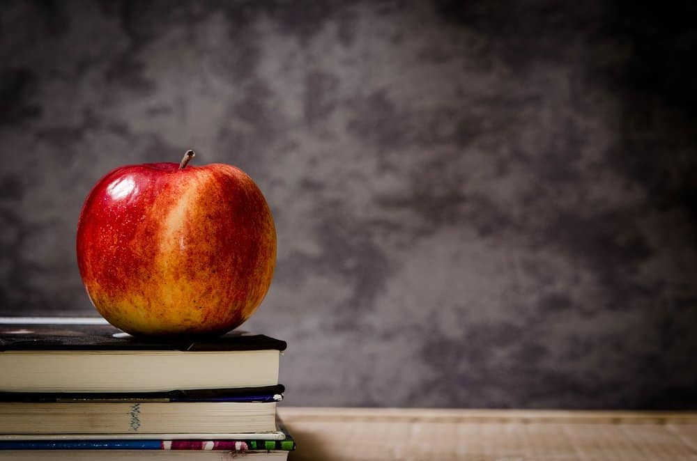 Red apple sitting on books
