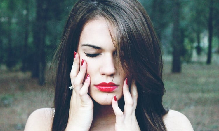 Brunette woman with red lipstick touches her fingers to the sides of her face due to sensitive teeth while standing in a forest
