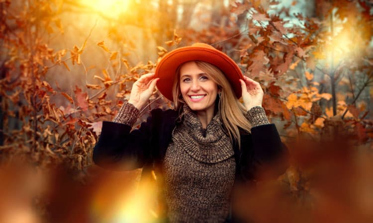 Middle-aged woman with dental implants smiles as she wears a red hat and sweater by trees with fall leaves