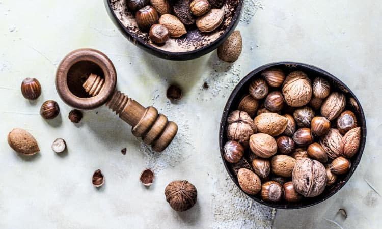 Aerial view of 2 bowls of uncracked nuts, a great holiday treat, next to a nut-cracker